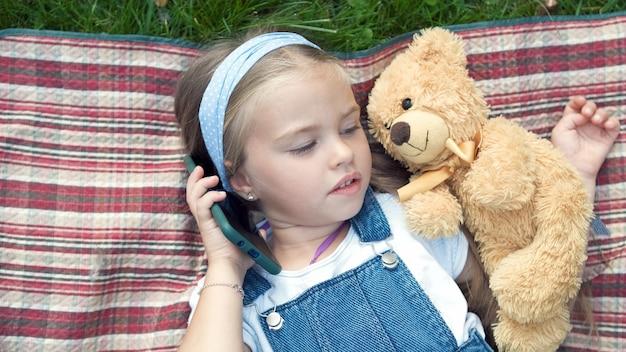 Klein mooi kindmeisje dat in de zomer op een deken op groen gazon ligt met haar teddybeerspeelgoed dat op mobiele telefoon praat.