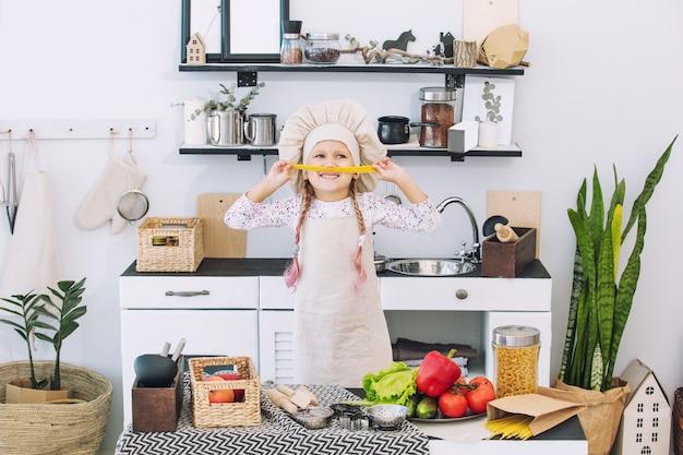 Klein mooi kindmeisje kookt in de keuken met verschillende groenten en spaghetti