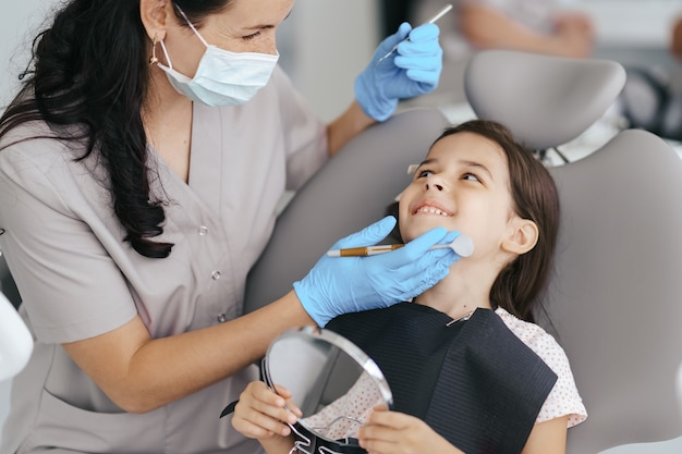Klein mooi meisje bij de tandarts lacht