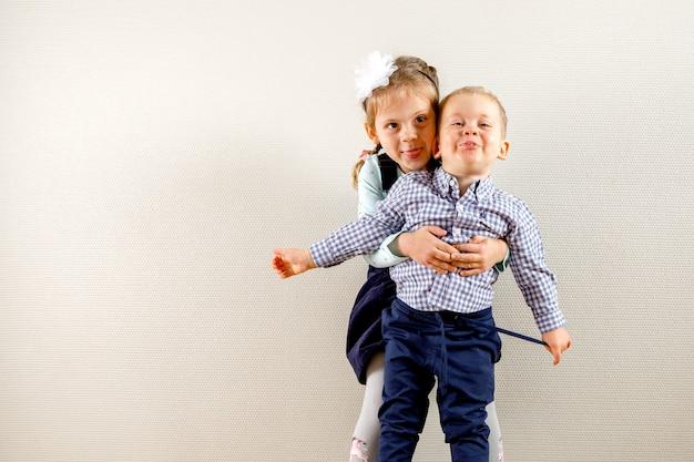 Klein mooi meisje dat zich dichtbij broer bevindt en hem koestert terwijl beiden glimlachen en gelukkig zijn