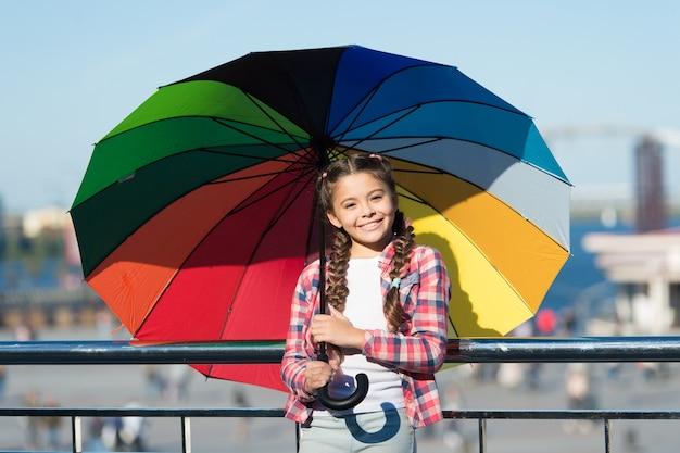 Klein mooi meisje dat zich met kleurrijke paraplu bevindt. meisje op brug. verbergen van de zon met paraplu. heldere tinten van de gelukkige stemming van het meisje. wachten op regen onder paraplu.