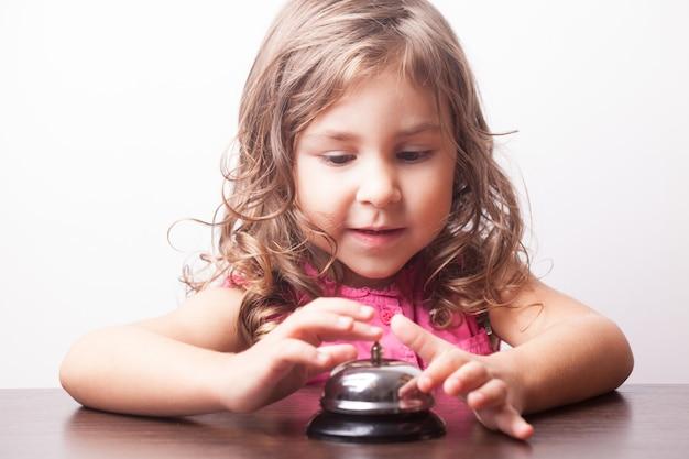 Klein mooi meisje druk op de bel, bordspel op tijd