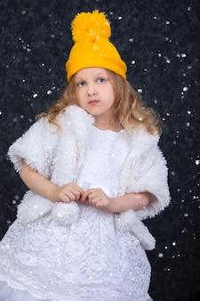 Klein mooi meisje in een gele gebreide muts en elegante witte jurk onder witte sneeuw.