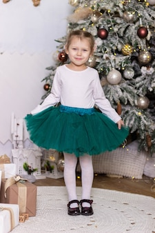 Klein mooi meisje in een groene tule rok staat en glimlacht bij de kerstboom