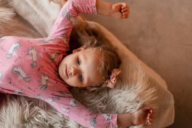 Klein mooi meisje in een modieuze kinderjurk met een pony ligt en rust op het bed, bovenaanzicht