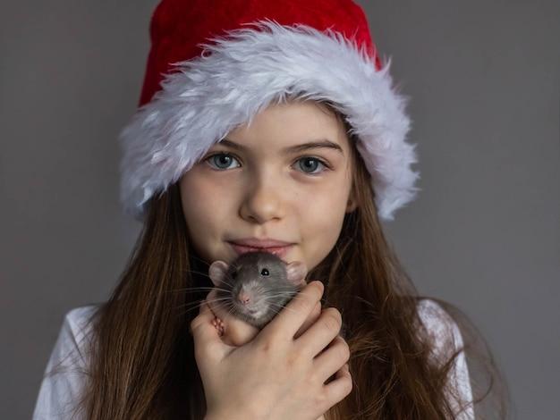 Klein mooi meisje in een new years-pet houdt in haar handen een decoratief binnenlands rat-symbool van nieuwjaarsportret