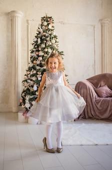 Klein mooi meisje in grote schoenen dansen in de buurt van de kerstboom
