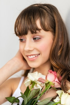 Klein mooi meisje in roze houdt het boeket rozen. close-up van de bloemen en het gezicht, kleine ballerina met een boeket