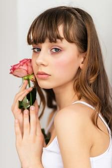 Klein mooi meisje in roze houdt het boeket rozen. sluit de bloemen en het gezicht, kleine ballerina met een boeket, mooi klein meisje met roze roos