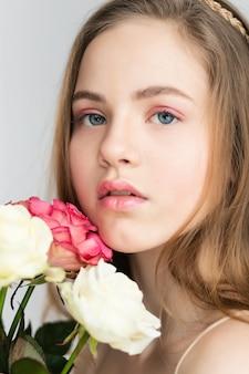 Klein mooi meisje in roze houdt het boeket rozen. sluit de bloemen en het gezicht