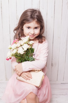 Klein mooi meisje in roze houdt het boeket rozen vast. kleine dame zittend op een stoel