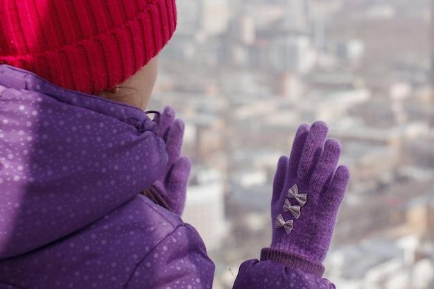 Klein mooi meisje met een lange vlecht in een paarse hoed met een pompon glimlacht en kijkt uit het raam. sluit omhoog