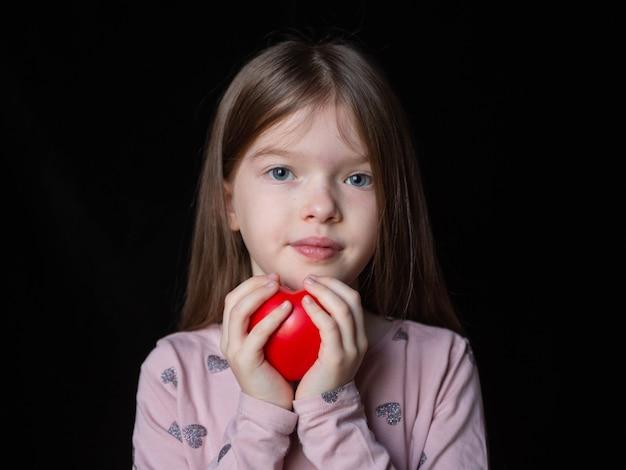 Klein mooi meisje met een rood hart, portret
