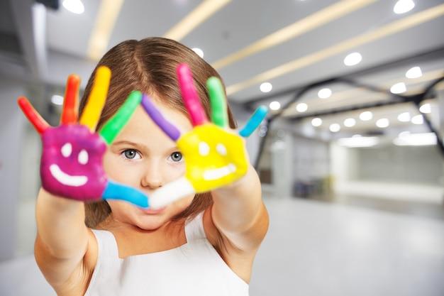 Klein mooi meisje met geschilderde handen