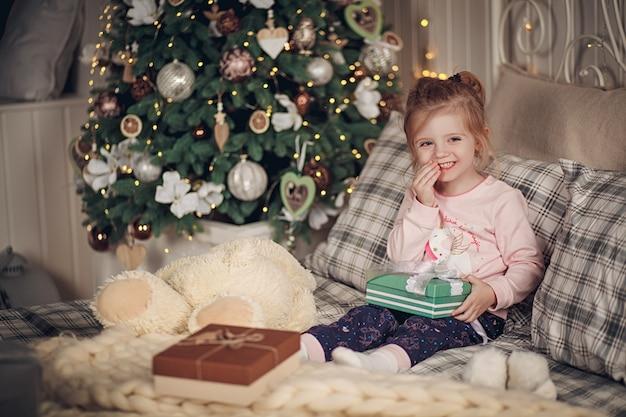 Klein mooi meisje met haar cadeautjes zit in haar bed