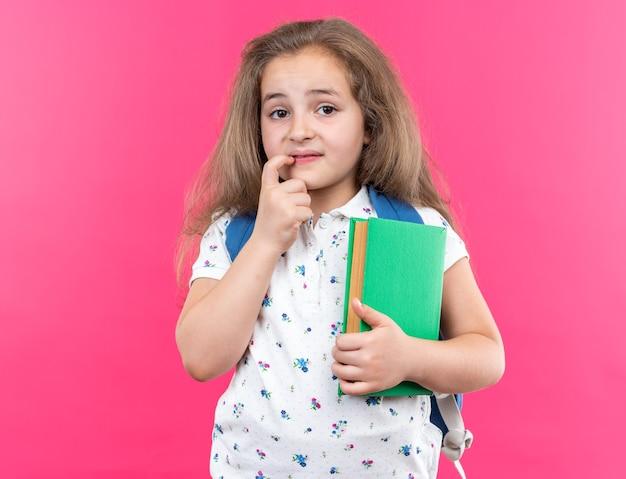 Klein mooi meisje met lang haar met een rugzak die een notitieboekje vasthoudt en naar de voorkant kijkt, nerveus en bezorgd bijtende nagels die over een roze muur staan