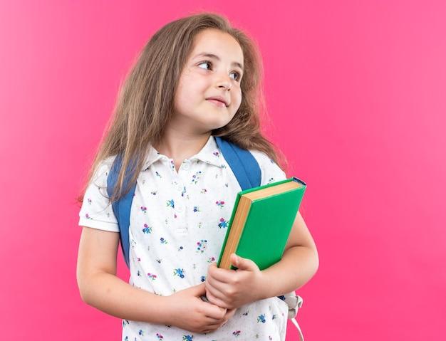 Klein mooi meisje met lang haar met een rugzak die een notitieboekje vasthoudt en opzij kijkt met een glimlach op een blij gezicht dat over een roze muur staat