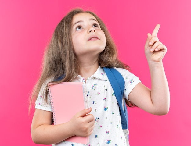 Klein mooi meisje met lang haar met rugzak die een notitieboekje vasthoudt en geïntrigeerd opkijkt, wijzend met de wijsvinger die over de roze muur staat