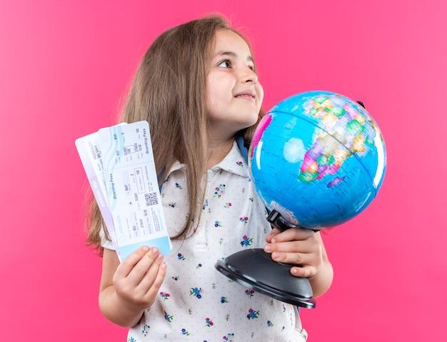 Klein mooi meisje met lang haar met rugzak met globe en vliegtickets opzij kijkend met een glimlach op een blij gezicht dat over een roze muur staat