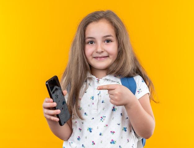 Klein mooi meisje met lang haar met rugzak met smartphone die met wijsvinger erop wijst en vrolijk glimlachend op oranje staat