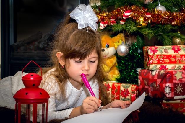 Klein mooi meisje schrijft een brief aan de kerstman in de buurt van de kerstboom.