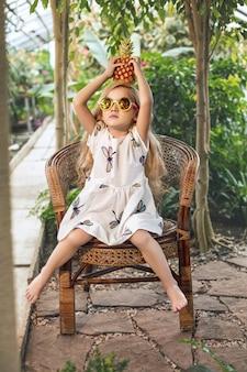 Klein mooi schattig babymeisje in witte jurk en zonnebril met ananas in handen