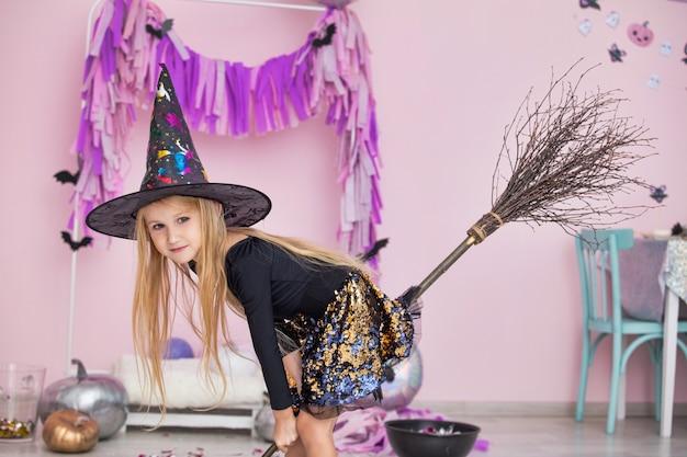 Klein mooi schattig kindmeisje in heksencarnavalkostuum in modieuze halloween-decoraties