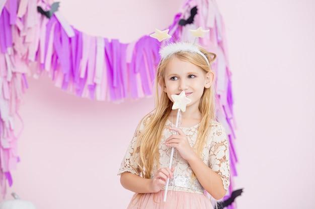 Klein mooi schattig kindmeisje in sprookjescarnavalkostuum in modieuze halloween-decoraties