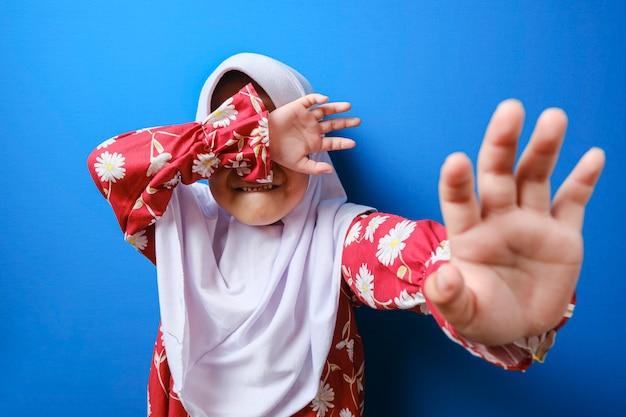 Klein moslimmeisje dat gepest wordt, steekt haar handpalm op en vraagt om het geweld te stoppen