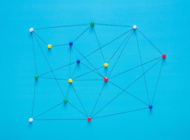 Klein netwerk van punaiseaansluitingen opstelling van kleurrijke pinnen gekoppeld aan een touwtje