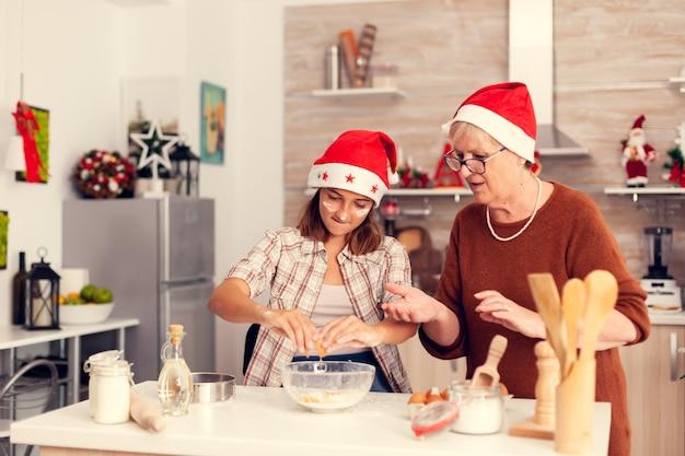 Klein nichtje tijdens kerstdag koken en plezier maken