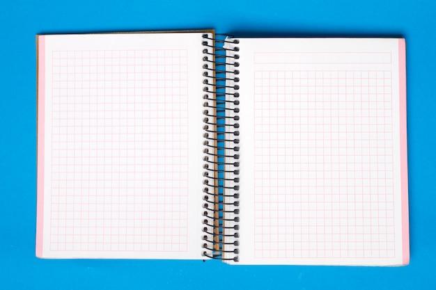 Klein notitieboekje over een blauwe achtergrond.