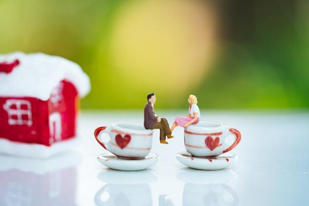 Klein paar figuur verliefd op koffiekopje met rode huis.