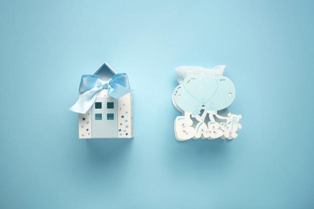 Klein papieren blauwe huis als de playneck en kind houten speelgoed met ballonnen op de blauwe achtergrond