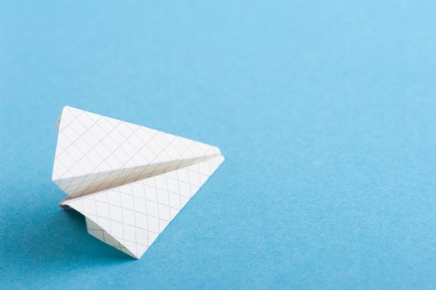 Klein papieren vliegtuigje op blauw