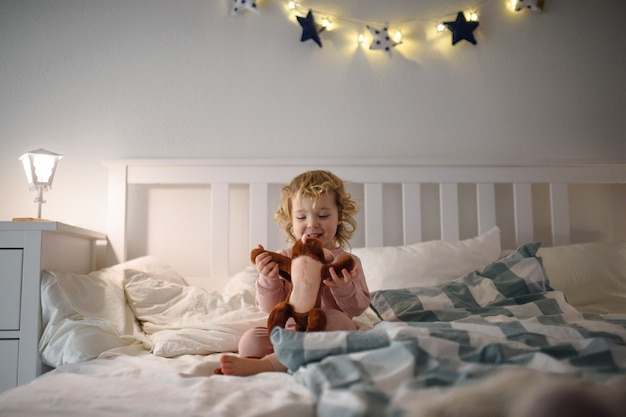 Klein peutermeisje dat thuis op bed zit en met zacht stuk speelgoed speelt.