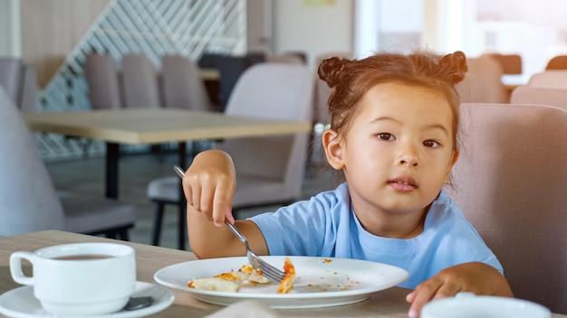 Klein peutermeisje in blauw t-shirt eet heerlijke pizza