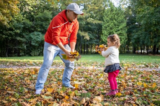 Klein peutermeisje speelt met vader buiten in herfstpark..