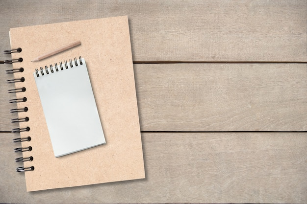 Klein potlood op leeg boek op houten lijst