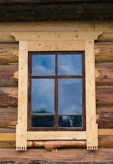 Klein raam in de muur van een oud houten huis oud historisch huis