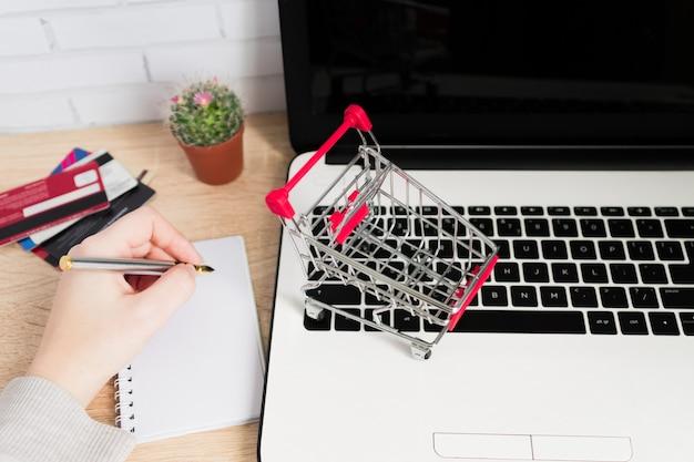 Klein rood boodschappenwagentje of karretje op laptop toetsenbord en vrouwenhand die in nota's schrijven. technologie bedrijfs online het winkelen concept