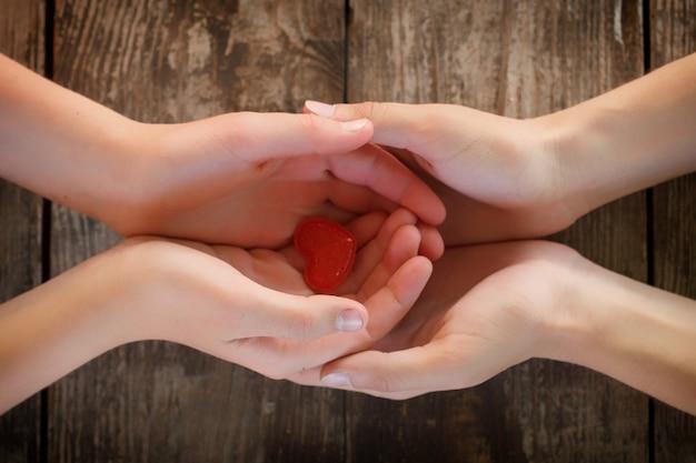 Klein rood hart ligt in de handen van mannen en vrouwen, het concept van liefde en romantiek.