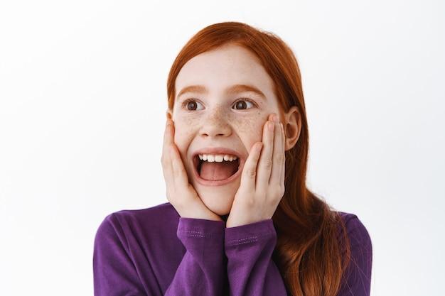 Klein roodharig meisje kijkt verrast en gelukkig opzij, verbaasd over super cool ding, glimlachend onder de indruk of gefascineerd, staren met bewondering naar banner, witte muur