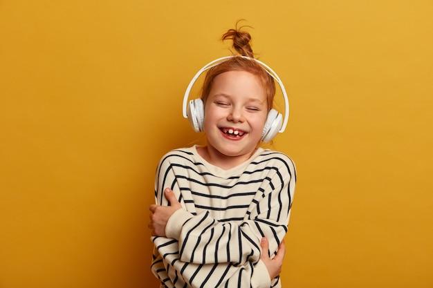 Klein roodharig meisje knuffelt zichzelf, lacht en heeft plezier, luistert naar muziek in een stereohoofdtelefoon, draagt een gestreepte trui, poseert over de gele muur, besteedt vrije tijd aan favoriete hobby, voelt zich geamuseerd