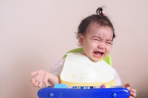 Klein schattig aziatisch babymeisje dat huilt met tranen op haar gezicht tijdens het eten, verdriet en ongelukkig, baby-uitdrukkingsconcept