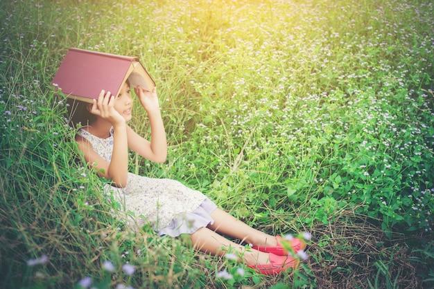 Klein schattig aziatisch meisje cover van het boek op haar hoofd op de natuur.