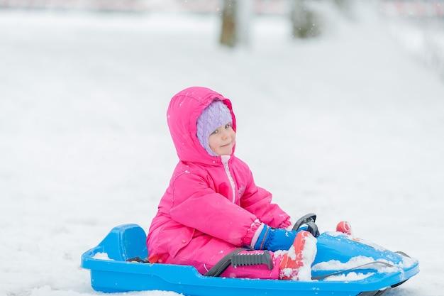 Klein schattig blauwogig meisje rodelen in een besneeuwd bos. wintertuin. bomen in de sneeuw.