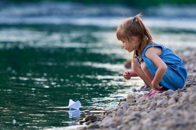 Klein schattig blond langharig meisje in blauwe jurk op rivieroever kiezelstenen spelen met boot van de witboekorigami op blauwe fonkelende bokeh waterscène. dromen en fantasieën van gelukkige jeugd concept.