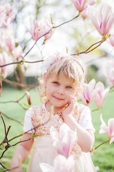 Klein schattig blond meisje 3 jaar oud speelt in een park in de buurt van een bloeiende magnolia. lente.