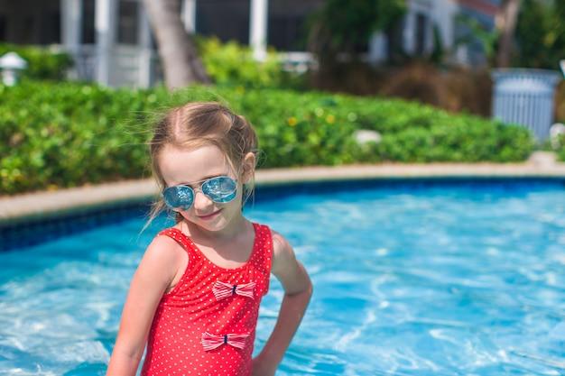 Klein schattig gelukkig meisje zwemt in het zwembad